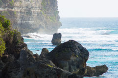 Rock in the sea. Bali, Indonesia. Rock in the sea against the background of cliffs. Bali, Indonesia Royalty Free Stock Photo
