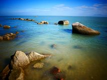 Rock, sea and blue sky - Penang, Malaysia. This is Batu Ferringhi Beach at Penang, Malaysia Stock Photos