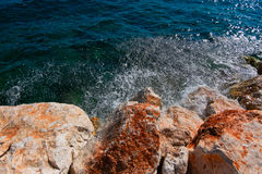Rock and sea with copyspace on blue sea surface Royalty Free Stock Photos