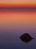 A rock in the sea at sunset Royalty Free Stock Photography