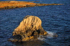 Rock in the sea at sunset royalty free stock photos
