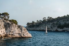 Rock, sea, trees and sailboat of Provence. Horizontal royalty free stock photos
