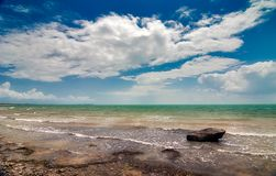 Rock in the sea under clouds Stock Photo