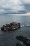 Rock in the sea. A rock in the sea. View from the promenade of the city of Sukhum , Abkhazia . Black Sea. impending storm Royalty Free Stock Photos
