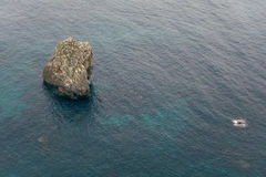 Rock in the sea, the view from the top of the waves and cliffs, turquoise waters Stock Images
