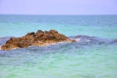 Rock among sea water Stock Photos