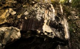 Rock sediment at Hetch Hetchy National Park. Over tunnel entry. Dark and mossy Royalty Free Stock Photos