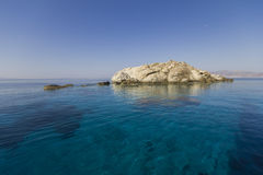 Rock in the shallow turquoise water, cyclades, Greece Stock Image