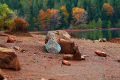 Rock on the shore of calm lake Stock Photography