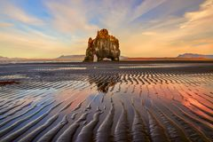 Rock on the shore of the ocean of an interesting unusual shape at low tide. Interesting symmetrical lines on the sand. Iceland. sea landscape. Places of stock image