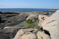 Rock shore at peggys cove, Nova Scotia. Rock formations with a green puddle at peggys cove, Nova Scotia stock photography