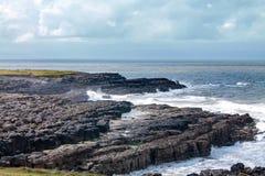 A rock shoreline Stock Images