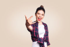 Rock sign. Happy funny toothy smiley young woman showing Rock sign with fingers. studio shot on beige background. Royalty Free Stock Photos
