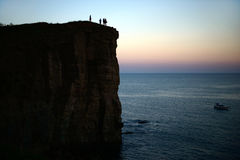 Rock silhouette with people on it and the sea in the sunset Stock Photography