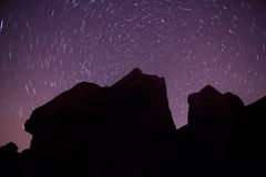 Rock silhouette and star trails round polaris. A rock silhouette with star trails at stanage edge round polaris Royalty Free Stock Photos