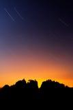 Rock silueteados y estrellas circumpolares Opinión hermosa de la noche sobre el acantilado de la piedra arenisca en el valle brum Imagenes de archivo