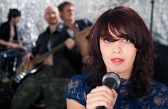 Rock singer with her band in the background Stock Photos