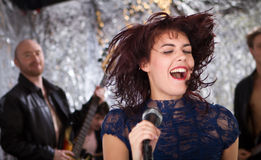 Rock singer with her band in the background Royalty Free Stock Photos