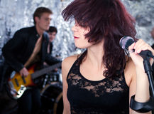 Rock singer with her band in the background Royalty Free Stock Photo