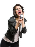 Rock singer with microphone and earphones. Half-length portrait of rock singer with earphones wearing leather jacket and keeping static microphone, isolated on stock photos