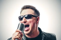 Rock singer with a microphone sings emotionally. Toned photo Stock Photography