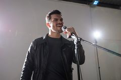 Rock singer performing on stage. Handsome male rock singer performing on stage with microphone Stock Photos