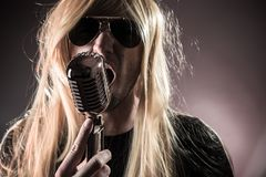 Rock singer with retro microphone Royalty Free Stock Image
