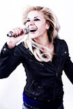 Rock singer. Young girl singing into microphone. Stock Photography