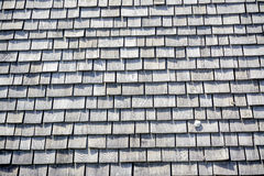 Rock sits on a wood shingled roof Royalty Free Stock Photography