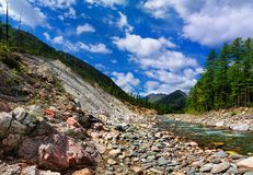 Rock slides near the river Stock Photos