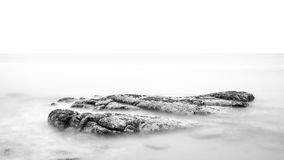 Rock in Smooth Calm Sea Stock Photo