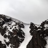 Rock with snow cornice in gray day. Turkey, Kachkar, highest part of Pontic Mountains Royalty Free Stock Photo