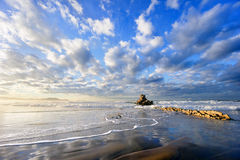 Rock in Sopelana beach with beautiful clouds. On sunny day stock photography
