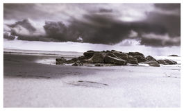 Black and white landscape of a rock formation on the beach with stormy skies above Royalty Free Stock Photography