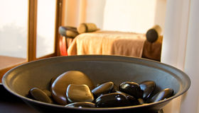 Rock spa. Spa room with rocks in bowl in foreground and treatment bed out of focus Stock Images
