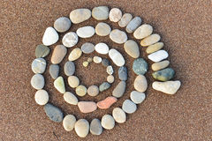 Rock spiral. A spiral design on the sand on a beach Stock Image
