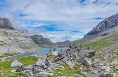 Gemmipass high. Rock stack with mountain, lake and beautiful summer sky on the background. City of Leukerbad-Gemmipass on 2200 meters high, canton Valais royalty free stock photography