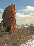 Rock stack in snowy landscape. Eroded red sandstone rock stack in snowy countryside with mountain range in background Royalty Free Stock Images