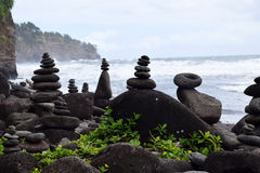 Rock stacks balancing on the Polulu black sand beach Royalty Free Stock Image