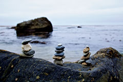 Rock Stacks on Beach. A stack of rock cairns in the foreground of the Pacific ocean on an overcast morning Royalty Free Stock Photography