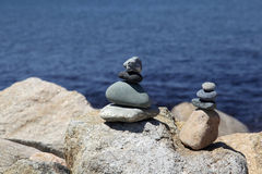 Rock stacks by blue sea. Two rock stacks on boulders by blue sea Royalty Free Stock Image