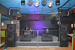 Rock stage for live music at a night club with lights and drums royalty free stock images