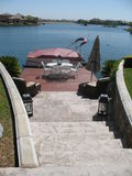 Rock Staircase, Redwood Patio Deck with Pontoon Boat on Lake. Rock Staircase leads to redwood patio deck with dining table and Chairs. Two lounge chairs are stock photography