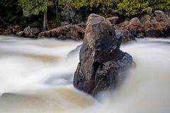 Rock Stands Solid In The Turbulent Waters Of Ragged Falls. Long exposure image of the Oxtongue River, adjacent to Algonquin Provincial Park in Ontario, Canada royalty free stock images