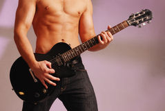 Rock star. Sexy male in jeans , shirtless and holding a black guitar Royalty Free Stock Photo