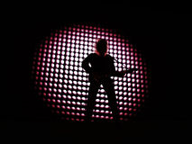 Rock star. A rocker silhouette with his guitar over a point backround Stock Photo