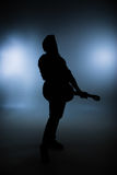 Rock Star. Silhouette of standing rock star with guitar in studio with white/blue background Stock Images