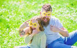 Rock star concept. Child and father posing with star shaped eyeglases photo booth attribute at meadow. Dad and daughter. Sits on grass at grassplot, green royalty free stock images