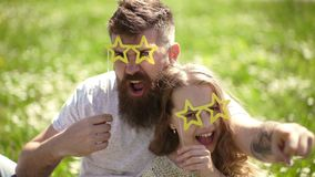 Rock star concept. Child and father posing with star shaped eyeglases photo booth attribute at meadow. Dad and daughter. Sits on grass at grassplot, green stock video footage