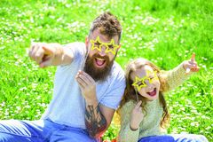 Rock star concept. Family spend leisure outdoors. Child and dad posing with star shaped eyeglases photo booth attribute. At meadow. Father and daughter sits on stock images